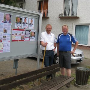 Zwei Kandidaten vor dem Schaukasten.