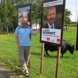 Dieter Gronert vor dem Plakat in Tonnenheide.